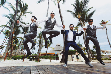 Happy groom and groomsmen jump on the way along the palms
