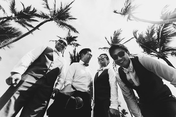 Stylish groom and groomsmen pose under tall green palms