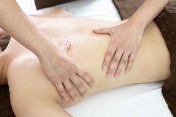 エステサロンでボディマッサージを受ける女性