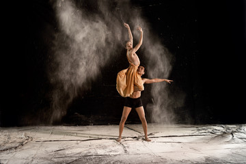 Young couple ballet dancing with powder in the stage