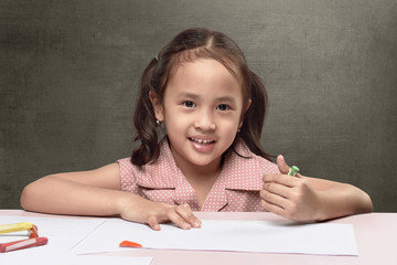 Cute asian little girl drawing on white paper
