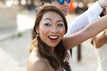 Cheerful Asian bride raises her hand up