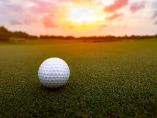 Golf ball on the green grass in beautiful golf course at sunset background, happy golf game