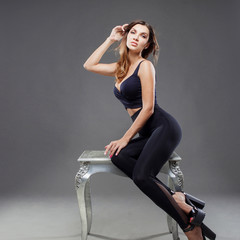 Beautiful sexy brunette woman sitting on a chair. Portrait on gray background