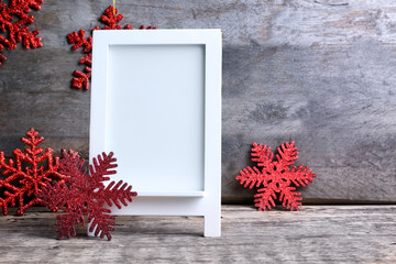Trendy Christmas decorations and photo frame on wooden background