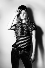 Cheerful model in black cap posing in studio