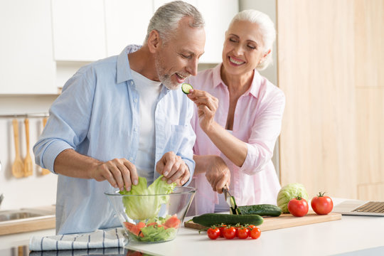 Mature loving couple family using laptop and cooking salad