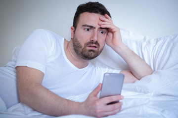 Man reading bad news on the mobile phone