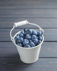 Blueberries in white bucket over black wooden background