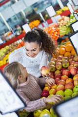 Mother and little daughter choosing seasonal fruits