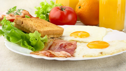 Healthy breakfast with bacon, eggs,toast and glass of juice