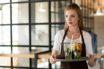 portrait of young waitress in apron holding tray with refreshing drinks in cafe