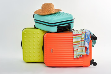 Bags for clothes for vacation. Suitcases, strawy hat, clothes. Preparation for summer recreation.