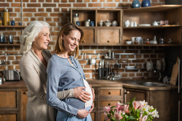 Portrait of young pregnant woman and her senior mother on kitchen