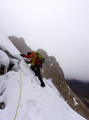 single male mountain climber ascending a steep glacier on a high altitude mountain face in the Cordillera Blanca in the Andes in Peru during bad. weather