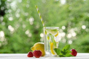 glass with lemonade on wooden table. outdoor photo