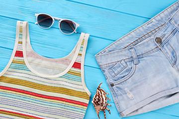 Female stylish clothing for beach. Shirt, sunglasses, denim shorts, sea shell. Concept of beach resort.