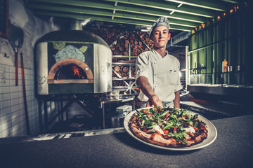 Food concept. Preparing traditional italian pizza. Young smiling chef in white uniform and gray hat show ready dish with green rucola herbs in interior of modern restaurant kitchen. Ready to eat.