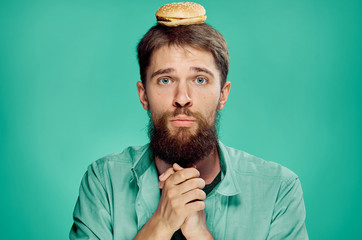 Man with a beard on a green background holds a hamburger