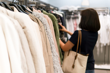 Woman is buying clothes. By ignoring the closet of her home that no to keep clothes again.