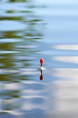 Fishing float on water with waves and beautiful reflection