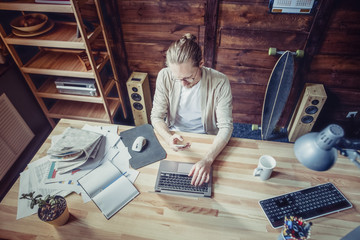 Top view on freelancer man sitiing at wooden table. Male sitting at wooden table typing on laptop with one hand, holding phone in another.