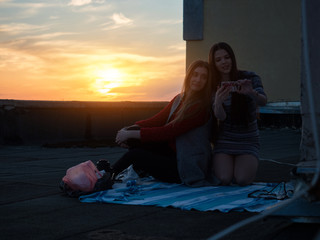 Girlfriends on the roof are photographed against the sunset. The roof of a house