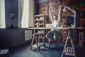 Freelancer man at his home office. Young man working online streching hands up.