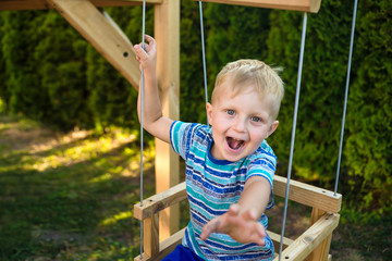 A small boy himself rolls on a seesaw without parental supervision