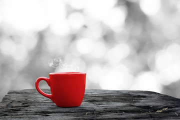 Hot drink in a red cup on grunge wood and White grey bokeh blurred background