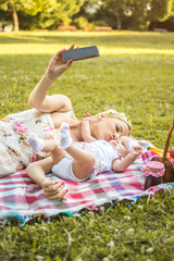 Young mother taking selfie while kissing her baby daughter in the park.