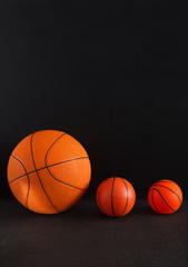 Big and small basketball balls on black background