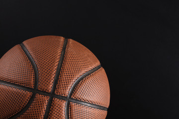 Old basketball ball on black background copy space