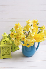 Spring daffodils or narcissus flowers in  blue pitcher and decorative green lanterns