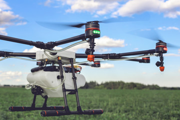 Closeup view of flying professional drone quadrocopter at the green field. Wall mural