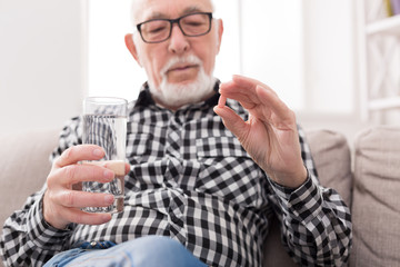 Old man having a glass of water and pills in hand