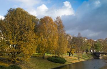 River in golden autumn city park.