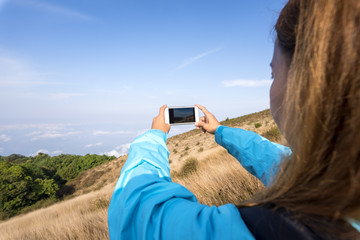 traveler use smartphone take a picture mountain landscape view