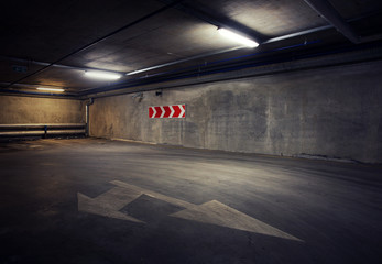 Urban underground background. Concrete wall under the lamp light in the dark with white arrow on the ground.