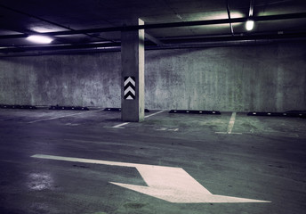 Empty dark abstract concrete room interior with white arrow. Architectural background.
