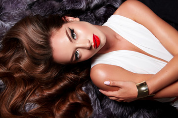 Beautiful young girl with a bright make-up in white body and long shiny wavy hair lies on a fur coat. Beauty, fashion, gold jewelry, beauty salon, cosmetics, makeup, clothing.