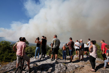 People look at smoke that rises from trees in woods near Seillons, in the Var department