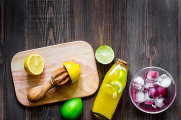 Making lemonade. Cookware, fruits, bottle of lemonade on wooden table background top view copyspace