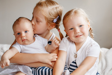 Lifestyle portrait of cute white Caucasian girls sisters holding kissing little baby, sitting on bed indoors. Older siblings with younger brother sister newborn. Family love bonding together concept.