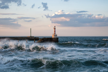 Red And White Lighthouse in Stormy Seas