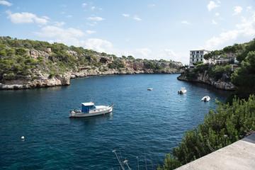 felsige Bucht auf Mallorca mit Schiffen in der Sonne
