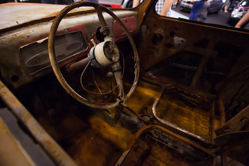 Rusty interior of an old car. Close up of Car steering wheel and dashboard panel with rust and dust.
