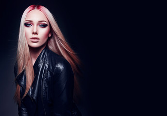 Beautiful blonde girl in black leather jacket and pink hair in rock style on black background.Makeup, cosmetics, hair care, hair dye, pink color. Fashion clothes. Fashion, beauty, rock, style, gothic.