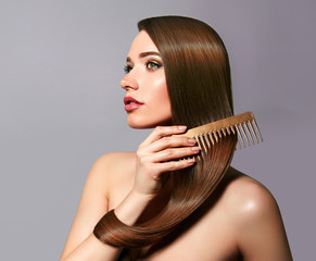 A beautiful young girl with long shiny silky hair sits and combs her hair with a golden comb. Cosmetics for hair, care, spa, beauty, fashion. Beauty saloon. Smooth skin. Advertising. Radiance, shine.