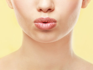 Closeup view of beautiful young woman with natural lips makeup on color background